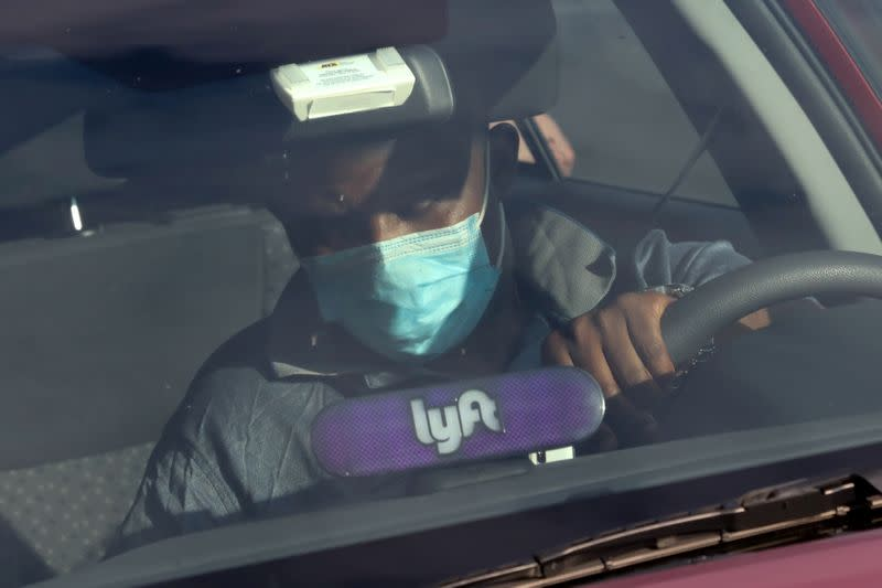 FILE PHOTO: A Lyft rideshare driver wears a mask as he leaves passengers in the U.S. Capitol Hill neighborhood in Washington