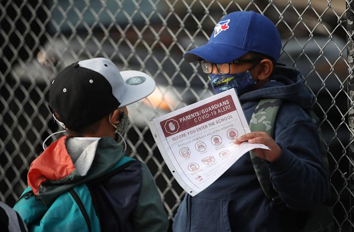 A student in Toronto looks over his COVID-19 Screening Passport while waiting in line to enter his school. (Credit: Steve Russell/Toronto Star via Getty Images)