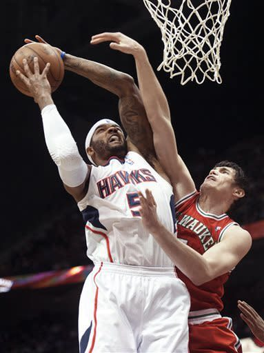 Atlanta Hawks forward Josh Smith, left, is fouled by Milwaukee Bucks forward Ersan Ilyasova (7), of Turkey, during the first half of an NBA basketball game, Friday, April 12, 2013, in Atlanta. (AP Photo/John Amis)