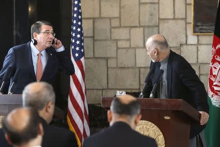 U.S. Secretary of Defense Ash Carter (L) listens to remarks by Afghan President Ashraf Ghani (R) during a joint news conference at the Presidential Palace in Kabul February 21, 2015.  REUTERS/Jonathan Ernst