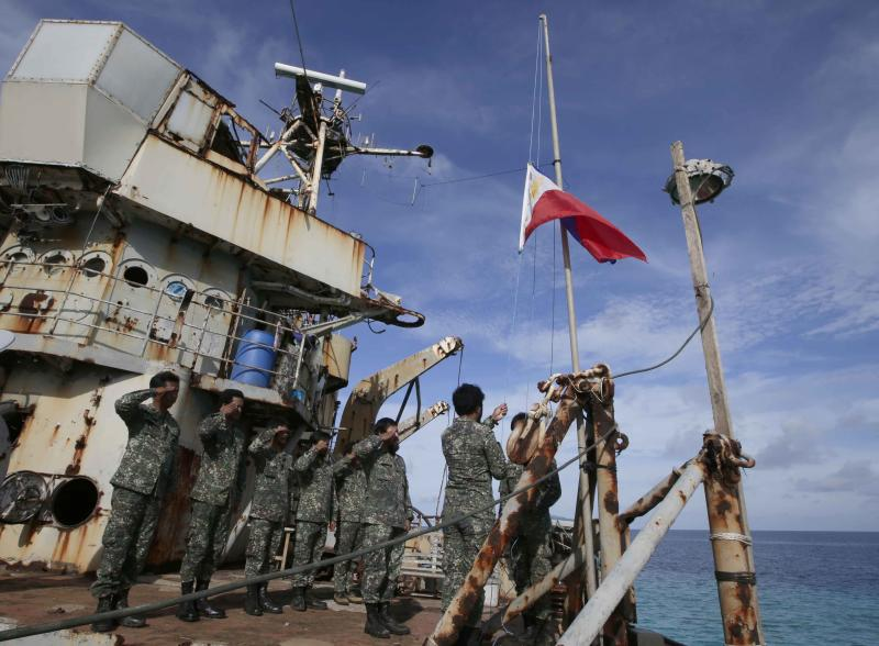 """FILE - Philippine Marines deployed on the Philippine Navy ship LT 57 Sierra Madre practice the """"relieving the watch"""" ceremony after the Philippine Government vessel AM700 successfully docked beside it off Second Thomas Shoal, locally known as Ayungin Shoal, in this March 29, 2014 file photo taken off South China Sea on the West Philippine Sea. The United States and the Philippines have reached a 10-year pact that would allow a larger U.S. military presence in this Southeast Asian nation as it grapples with increasingly tense territorial disputes with China, according to two Philippine officials and a confidential government primer seen by The Associated Press on Sunday April 27, 2014. (AP Photo/Bullit Marquez)"""