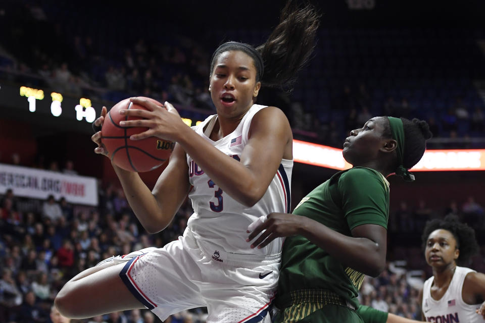 Connecticut's Megan Walker pulls down a rebound over South Florida's Bethy Mununga, right, during the first half of an NCAA college basketball game in the American Athletic Conference tournament seminfals at Mohegan Sun Arena, Sunday, March 8, 2020, in Uncasville, Conn. (AP Photo/Jessica Hill)