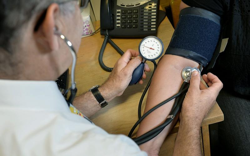 A GP checking a patient's blood pressure. GP practices in England have been reminded that they must make sure patients can access face-to-face appointments if they need them, as the coronavirus crisis continues - Anthony Devlin/PA