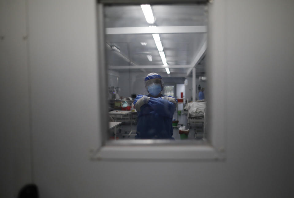 A doctor poses for a photo inside the intensive care unit designated for people infected with COVID-19 at a hospital in Mar del Plata, Argentina, Saturday, Oct. 10, 2020. Today, 65% of Argentina's cases are in its provinces, authorities said. (AP Photo/Natacha Pisarenko)