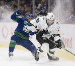 Vancouver Canucks left wing Tanner Pearson (70) fights for control of the puck with San Jose Sharks defenceman Mario Ferraro (38) during the third period of an NHL hockey game in Vancouver, British Columbia, Saturday, Jan. 18, 2020. (Jonathan Hayward/The Canadian Press via AP)