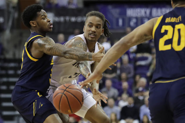 Washington forward Hameir Wright, center, passes the ball from between California guards Paris Austin, left, and Matt Bradley during the second half of an NCAA college basketball game Saturday, Feb. 22, 2020, in Seattle. Washington won 87-52. (AP Photo/Ted S. Warren)