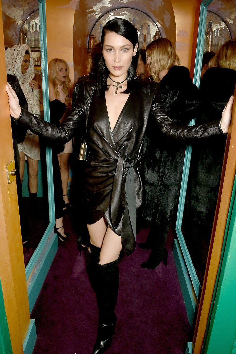 <p>In a leather wrap dress, over-the-knee boots and cross choker necklace at the LOVE and Burberry London Fashion Week Party. </p>