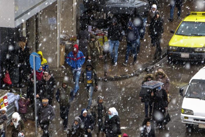In this photo released by the Syrian official news agency SANA, people walk on a street as snow falls, in Damascus, Syria, Wednesday, Feb. 17, 2021. Snow blanketed parts of Syria, Lebanon, Jordan and Israel on Wednesday, blocking roads, disrupting traffic and postponing vaccination campaigns against COVID-19 and even exams at some universities. (SANA via AP)