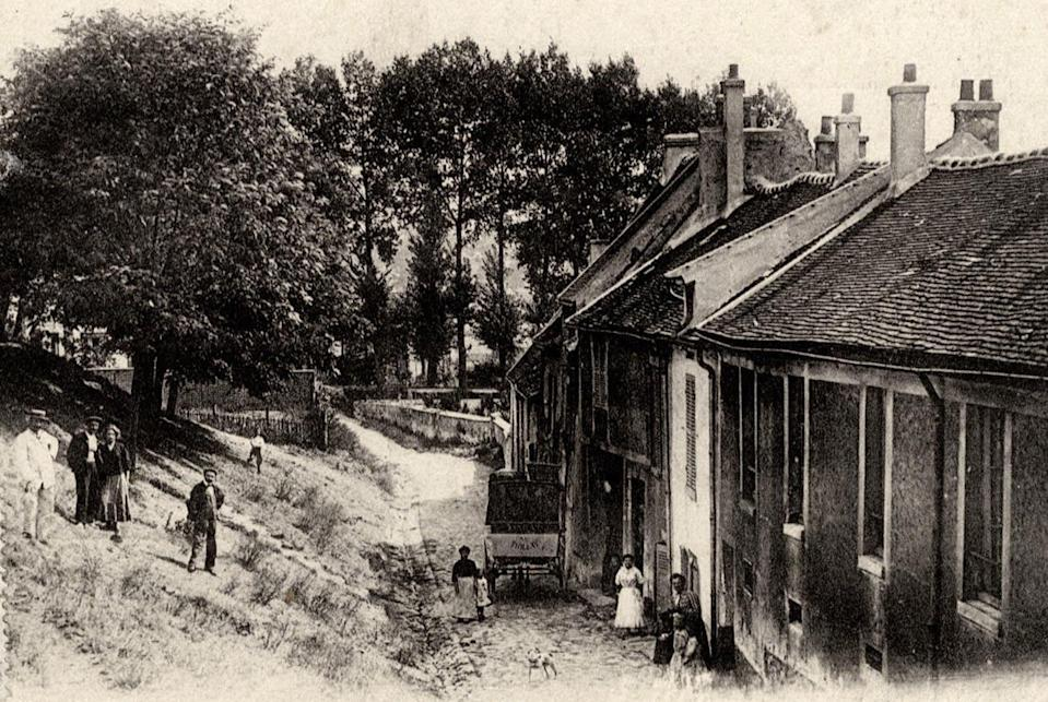 A vintage postcard printed around 1910 shows Gaudry street, with a dozen people walking down the road or milling on the grass. (Reuters)
