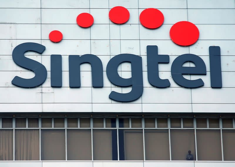 FILE PHOTO: A man looks out of the window under a Singtel signage at their head office in Singapore