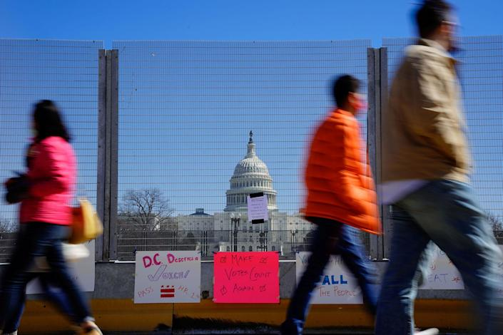 People walk past signs hung on a security fence in support of expanded voting rights near the U.S. Capitol in Washington
