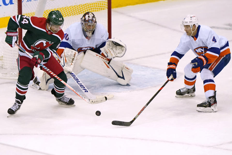New Jersey Devils left wing Miles Wood (44) sets up in front of New York Islanders goaltender Semyon Varlamov (40) with Islanders defenseman Andy Greene (4) nearby during the third period of an NHL hockey game Tuesday, March 2, 2021, in Newark, N.J. (AP Photo/Kathy Willens)