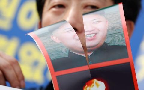North Korean defector Park Sang-Hak holds a defaced portrait of North Korean leader Kim Jong-Un during a rally against the South Korean government's policy on North Korea - Credit: EPA/JEON HEON-KYUN