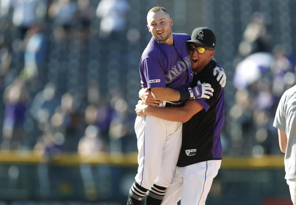 Colorado Rockies' Garrett Hampson, left, celebrates his walkoff RBI-single with Kyle Freeland in the 10th inning of a baseball game against the Miami Marlins, Sunday, Aug. 18, 2019, in Denver. (AP Photo/David Zalubowski)