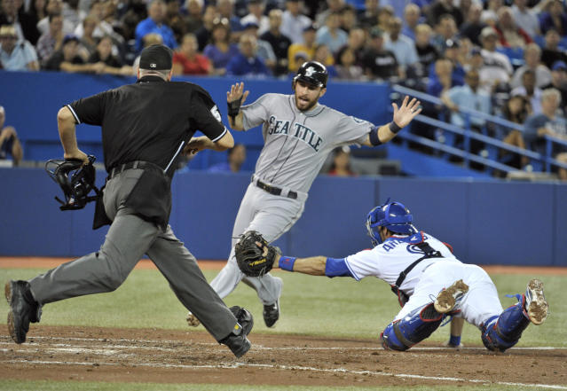 Seattle Mariners base runner Dustin Ackley (C) scores a run ahead of the tag by Toronto Blue Jays catcher J.P. Arencibia (R) as home plate umpire Paul Emmel follows the play during the fourth inning of their MLB American League baseball game in Toronto September 12, 2012. REUTERS/Mike Cassese (CANADA - Tags: SPORT BASEBALL TPX IMAGES OF THE DAY)