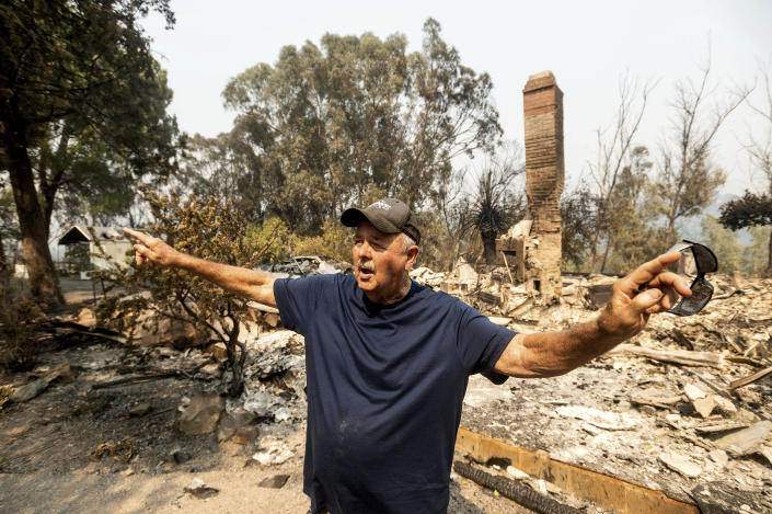 Hank Hanson, 81, describes the path the LNU Lightning Complex fires took to reach his Vacaville, Calif., home on Friday, Aug. 21, 2020. Hanson, who built the house thirty years ago, does not think he will rebuild. (AP Photo/Noah Berger)