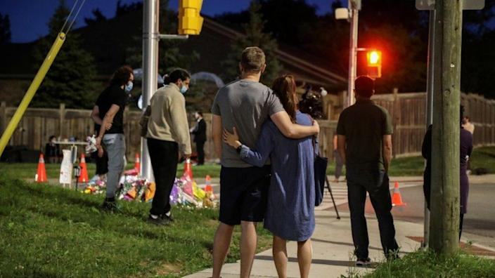 People react near flowers laid at the fatal crime scene in London, Ontario, Canada June 7, 2021