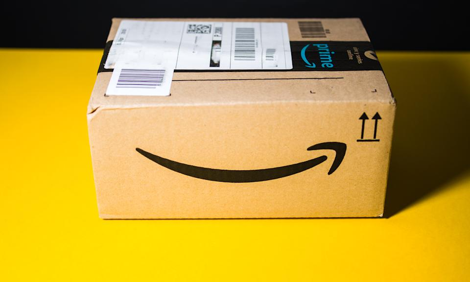 PARIS, FRANCE - SEP 28, 2018: Small Amazon parcel cardboard box against yellow background smile logo. Amazon Prime is the online paid subscription service offered by Amazon.com web-commerce site
