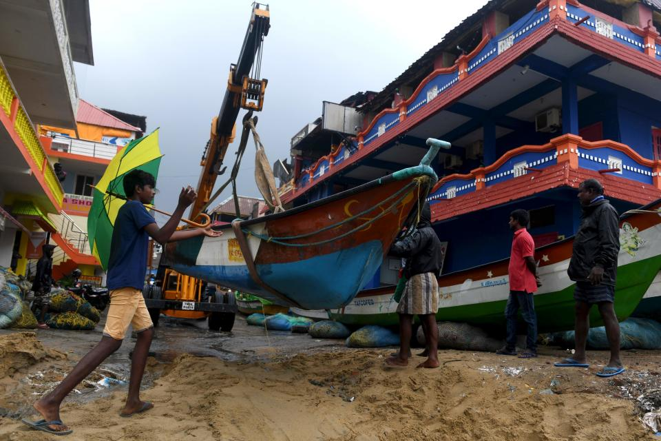 Fishermen move their boats as cyclone Nivar approaches. (Photo by ARUN SANKAR/AFP via Getty Images)