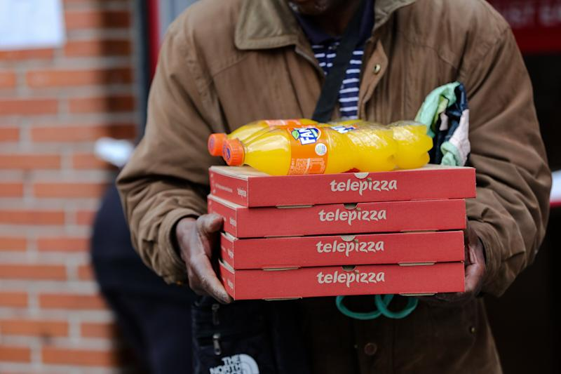 Un hombre recibe varias pizzas de Telepizza dentro del menú para familias desfavorecidas de la Comunidad de Madrid. (Photo: Europa Press News via Getty Images)