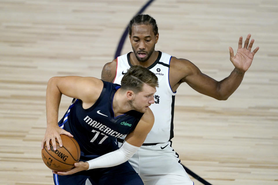Los Angeles Clippers' Kawhi Leonard, right, will face the Dallas Mavericks and Luka Doncic (77) in the first round of the playoffs. (AP Photo/Ashley Landis, Pool)