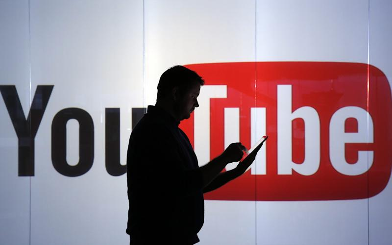 A man checks a mobile device while standing against an illuminated wall bearing YouTube's logo