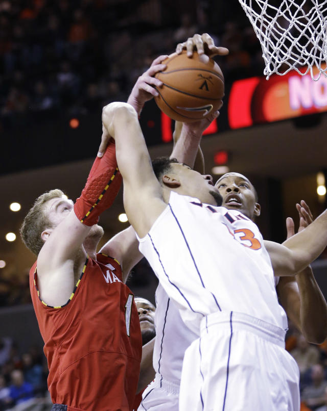 Virginia forward Anthony Gill, front, struggles for a rebound with Maryland forward Evan Smotrycz, left, and Virginia forward Darion Atkins, back, during the first half of an NCAA college basketball game in Charlottesville, Va., Monday, Feb. 10, 2014. (AP Photo/Steve Helber)