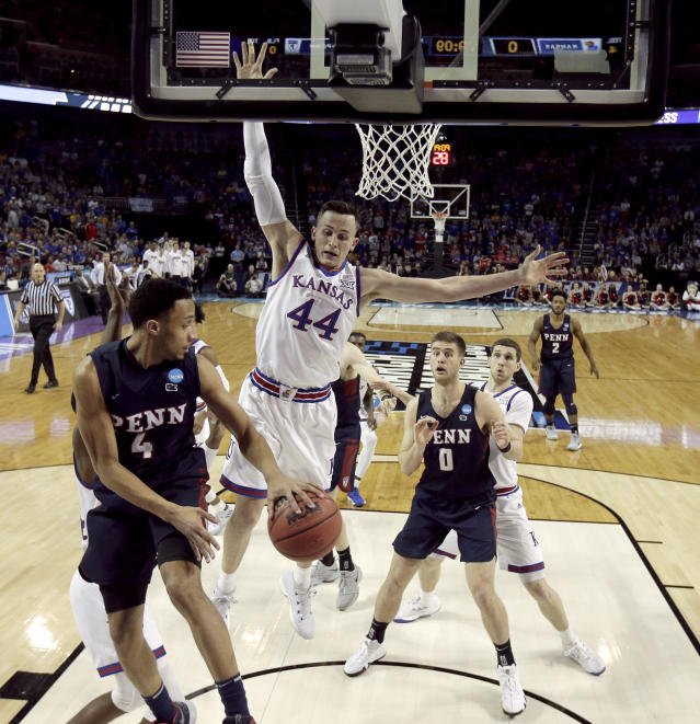 Pennsylvania guard Darnell Foreman (4) passes around Kansas forward Mitch Lightfoot (44) during the first half of an NCAA college basketball tournament first-round game Thursday, March 15, 2018, in Wichita, Kan. (AP Photo/Charlie Riedel)