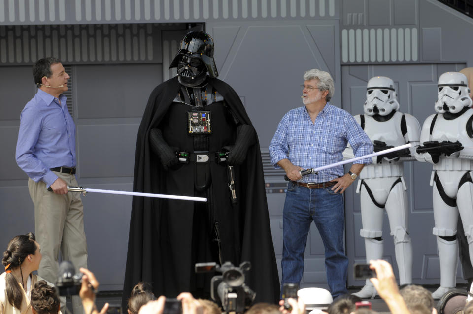 Disney CEO Robert Iger, left, an actor portraying the movie character Darth Vader, center, and Star Wars creator George Lucas, third from right, stand onstage at the Disney Hollywood Studios theme park during the re-opening celebration of the Star Tours motion simulation ride in Lake Buena Vista, Fla., Friday, May 20, 2011. (AP Photo/Phelan M. Ebenhack)