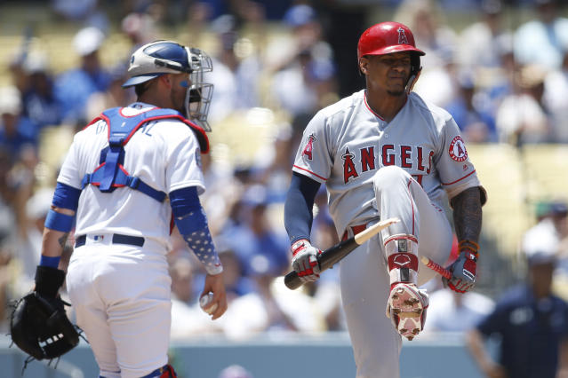 Los Angeles Angels Jefry Marte, right, breaks his bat over his leg after striking out on a full-count pitch from Los Angeles Dodgers starting pitcher Clayton Kershaw in front of Dodgers catcher Yasmani Grandal, left, to end the top of the first inning of a baseball game leaving the bases loaded Sunday, July 15, 2018, in Los Angeles. (AP Photo/Danny Moloshok)