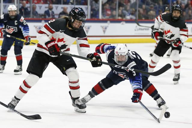 Canada's Meghan Agosta (2) and United States' Cayla Barnes (3) battle for the puck during the second period of a rivalry series women's hockey game in Hartford, Conn., Saturday, Dec. 14, 2019. (AP Photo/Michael Dwyer)