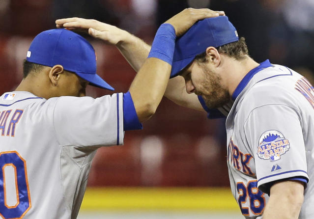 New York Mets second baseman Daniel Murphy (28) and shortstop Wilfredo Tovar pat each other on the head after they defeated the Cincinnati Reds 4-2 in a baseball game, Tuesday, Sept. 24, 2013, in Cincinnati. Murphy hit a three-run home run during the second inning of the game. (AP Photo/Al Behrman)