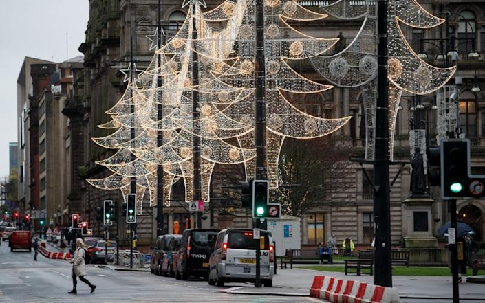 People walk in Glasgow city center ahead of the restrictions coming into force - Shutterstock