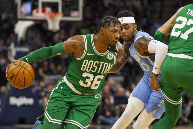 Boston Celtics guard Marcus Smart (36) drives on Minnesota Timberwolves guard D'Angelo Russell (0) in the second quarter of an NBA basketball game Friday, Feb. 21, 2020, in Minneapolis. (AP Photo/Andy Clayton-King)