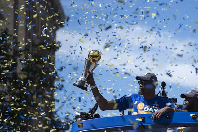 <p>Golden State Warriors forward Kevin Durant (35) hoists the MVP trophy during the Warriors 2017 championship victory parade in downtown Oakland. Mandatory Credit: Kyle Terada-USA TODAY Sports </p>