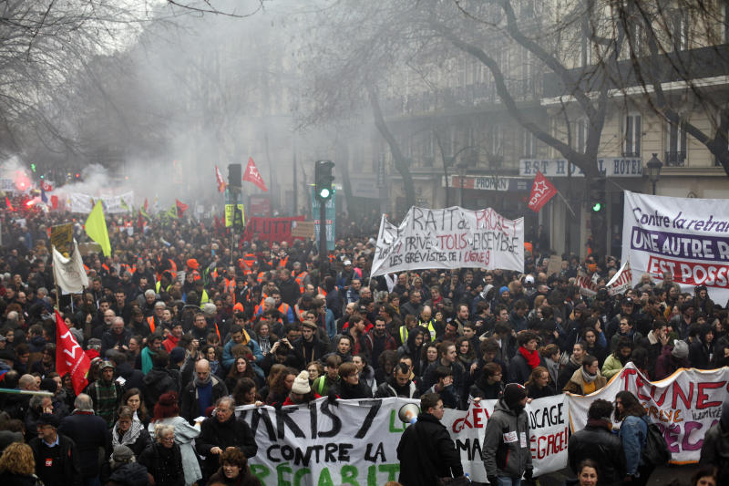 Striking workers march during a demonstration Thursday, Jan. 9, 2020 in Paris. Rail workers, teachers, doctors, lawyers and others joined a nationwide day of protests and strikes Thursday to denounce French President Emmanuel Macron's plans to overhaul the pension system. Banner reads: Striking until withdrawal. (AP Photo/Thibault Camus)