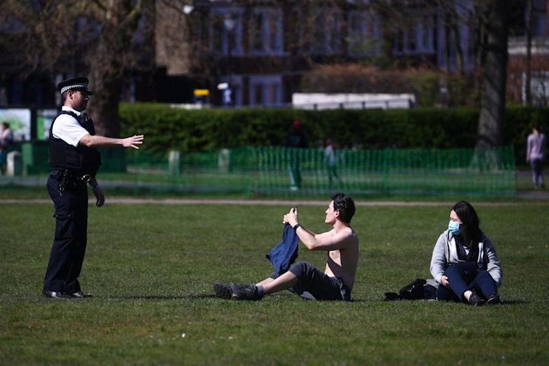A police officer speaks with people in Greenwich Park (REUTERS)