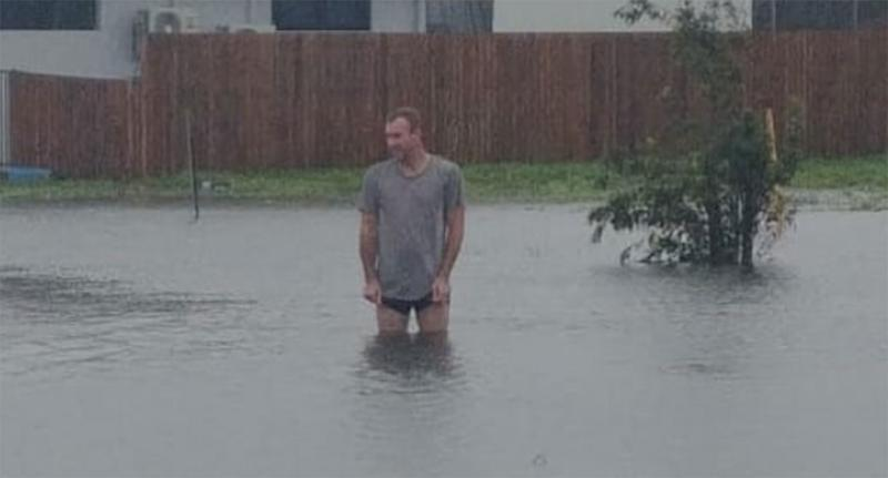 A man stands in waist-deep floodwaters in Ayr, Queensland.