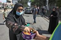 A Palestinian man in Gaza distributes sweets to celebrate the escape of six Palestinians from an Israeli prison (AFP/MOHAMMED ABED)