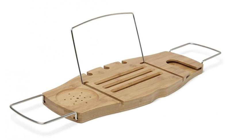 """Give your partner a break from the kids with this bathtub caddy, and the promise of some actual peace and quiet. Get it at <a href=""""https://www.chapters.indigo.ca/en-ca/house-and-home/umbra-aquala-bathtub-caddy-natural/028295188661-item.html"""" target=""""_blank"""" rel=""""noopener noreferrer"""">Indigo</a>, $50."""