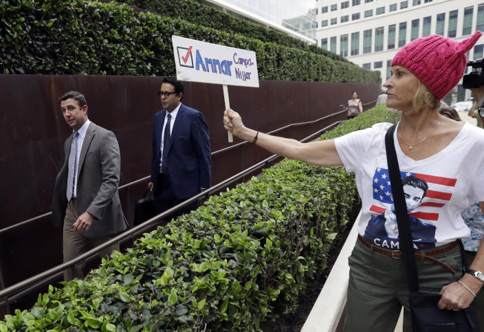 Rep. Duncan Hunter, left, leaves court as a woman holds a sign for his opponent, Ammar Campa-Najjar, on Sept. 24, 2018, in San Diego. (Photo: Gregory Bull/AP)