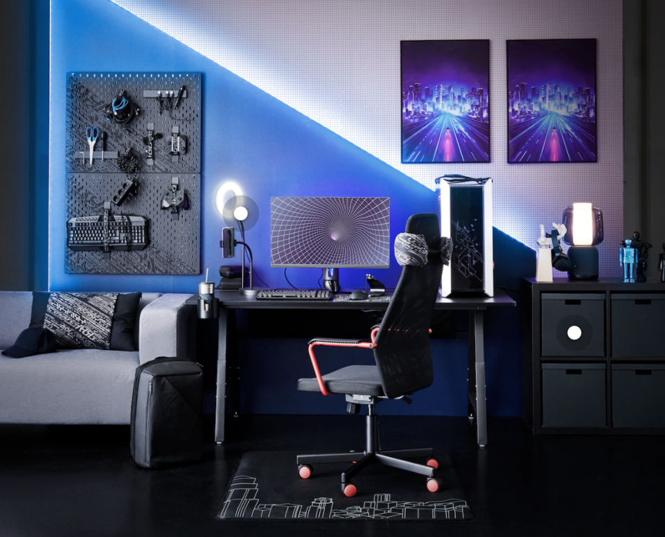 A blue hued room full of cyberpunk style gaming furniture.