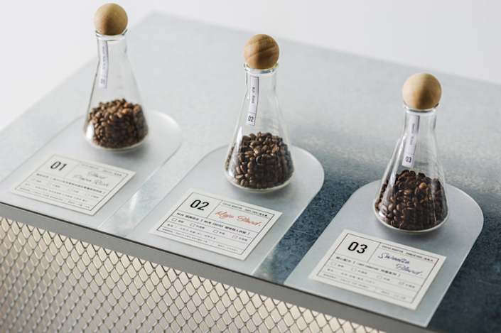 Coffee beans from all over the world sit in crystal clear test tubes inside iDrip's Smart Pour-Over Coffeemaker Exhibition Space.