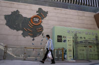 A woman wearing a face mask to help protect herself from the coronavirus walks by a map showing Evergrande development projects in China, at an Evergrande city plaza in Beijing, Tuesday, Sept. 21, 2021. Global investors are watching nervously as the Evergrande Group, one of China's biggest real estate developers, struggles to avoid defaulting on tens of billions of dollars of debt, fueling fears of possible wider shock waves for the Chinese financial system. (AP Photo/Andy Wong)