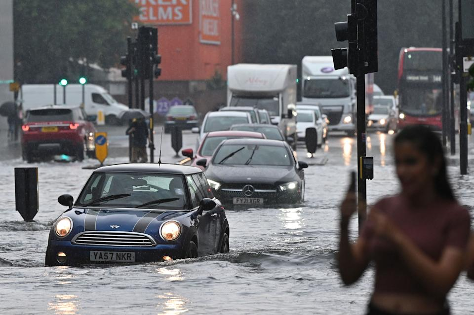 Cars are driven through deep water on a flooded road in The Nine Elms district of London on July 25, 2021 during heavy rain. - Buses and cars were left stranded when roads across London flooded on Sunday, as repeated thunderstorms battered the British capital. (Photo by JUSTIN TALLIS / AFP) (Photo by JUSTIN TALLIS/AFP via Getty Images)
