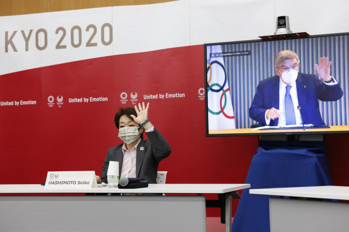 Tokyo 2020 President Seiko Hashimoto and IOC President Thomas Bach, on a screen, greet each other during a five-party online meeting at Harumi Island Triton Square Tower Y in Tokyo Monday, June 21, 2021. The Tokyo Olympics will allow some local fans to attend when the games open in just over a month, Tokyo organizing committee officials and the IOC said on Monday. (Rodrigo Reyes Marin/Pool Photo via AP)