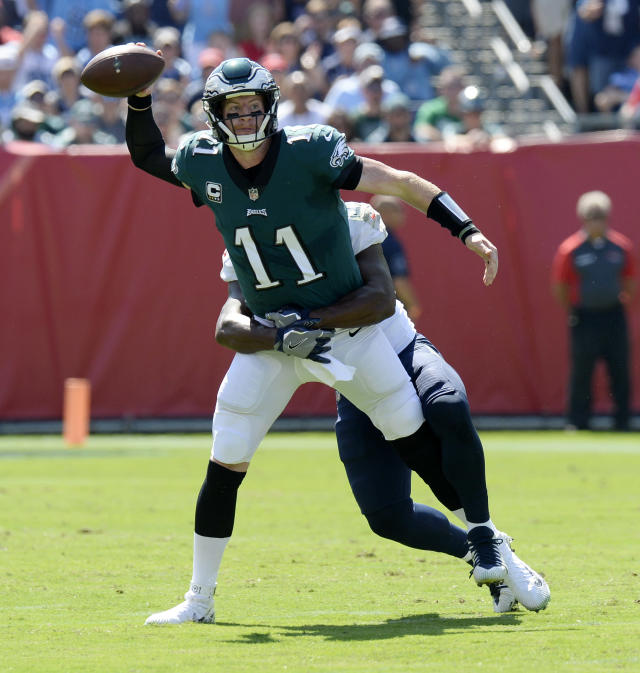 <p>Philadelphia Eagles quarterback Carson Wentz (11) throws a pass as he is grabbed by Tennessee Titans linebacker Jayon Brown in the first half of an NFL football game Sunday, Sept. 30, 2018, in Nashville, Tenn. (AP Photo/Mark Zaleski) </p>