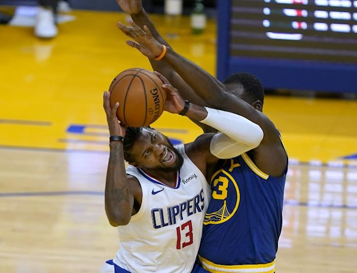 Los Angeles Clippers guard Paul George (13) reacts as he is fouled by Golden State Warriors forward Draymond Green (23) during the first half of an NBA basketball game in San Francisco, Friday, Jan. 8, 2021. (AP Photo/Tony Avelar)