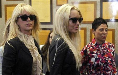 Actress Lindsay Lohan (C) stands with her mother Dina Lohan (L) and attorney Shawn Chapman Holley (R) as she waits to go through the metal detector at the Beverly Hills Municipal Courthouse July 20, 2010, where she is due to surrender for a 90-day jail sentence for violating the terms of her probation on drunk driving charges by missing alcohol education classes in Beverly Hills, California. REUTERS/Danny Moloshok