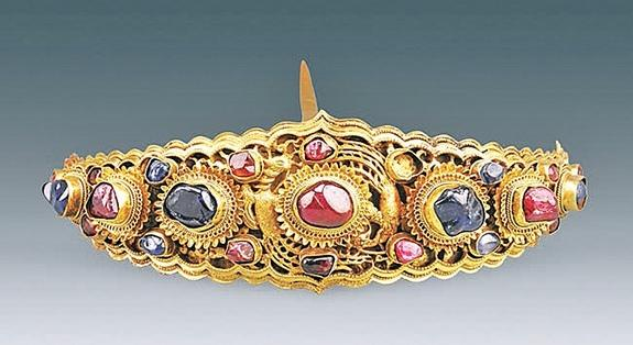 A gold hairpin, decorated with a mix of sapphires and rubies, found inside the Ming Dynasty tomb of a woman named Lady Mei.